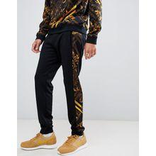Versace Jeans - Enge Jogginghose mit seitlichen Streifen mit Barockdesign in Gelb - Schwarz