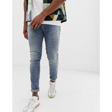 United Colors Of Benetton - Enge Jeans in mittlerer Waschung mit Rissen und Flicken - Blau